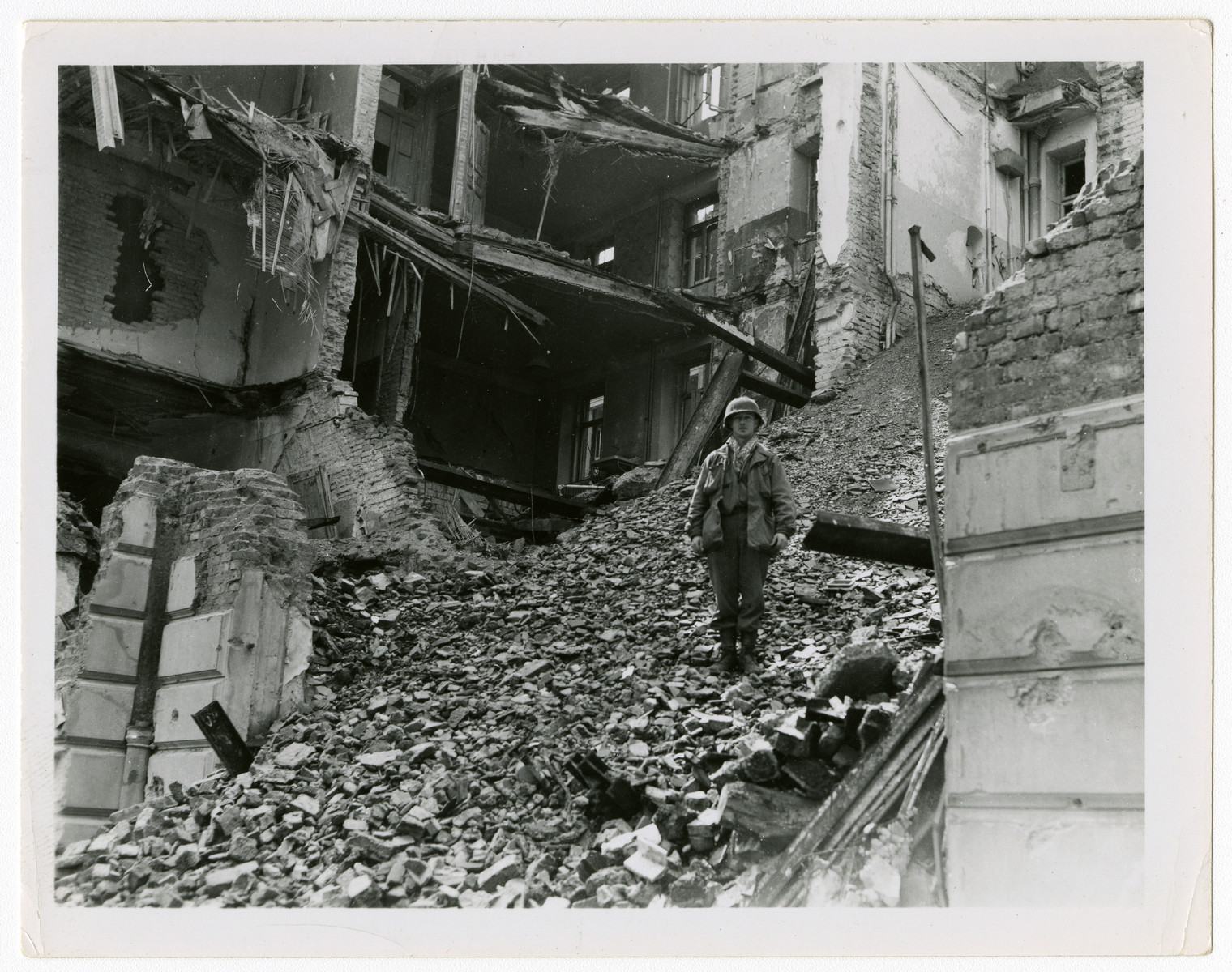 """An American soldier poses amidst the rubble of a bombed out street in Munich.  Original caption reads, """"This was Munich, May '45."""""""