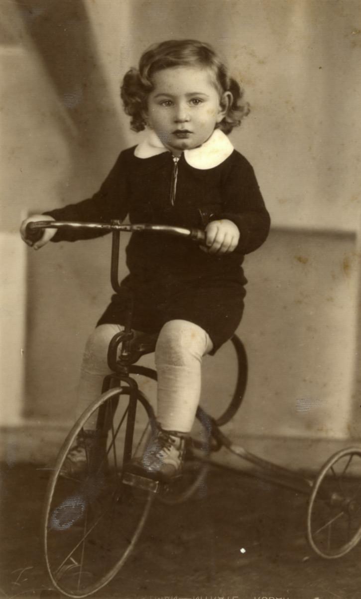 Studio portrait of Rysio Blass riding a tricycle.   Rysio Blass later perished in the Holocaust.