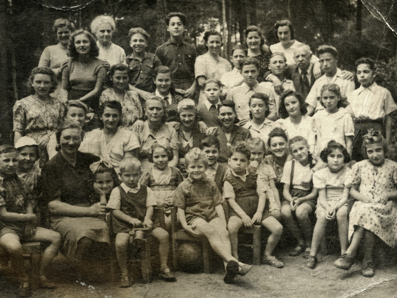 Group portrait of Jewish orphans and employees at the Lodz orphanage, a youth aliyah home.   Pictured in the second row, fourth from the right, wearing a dark jacket is orphanage councellor Rachel Greenfeld.