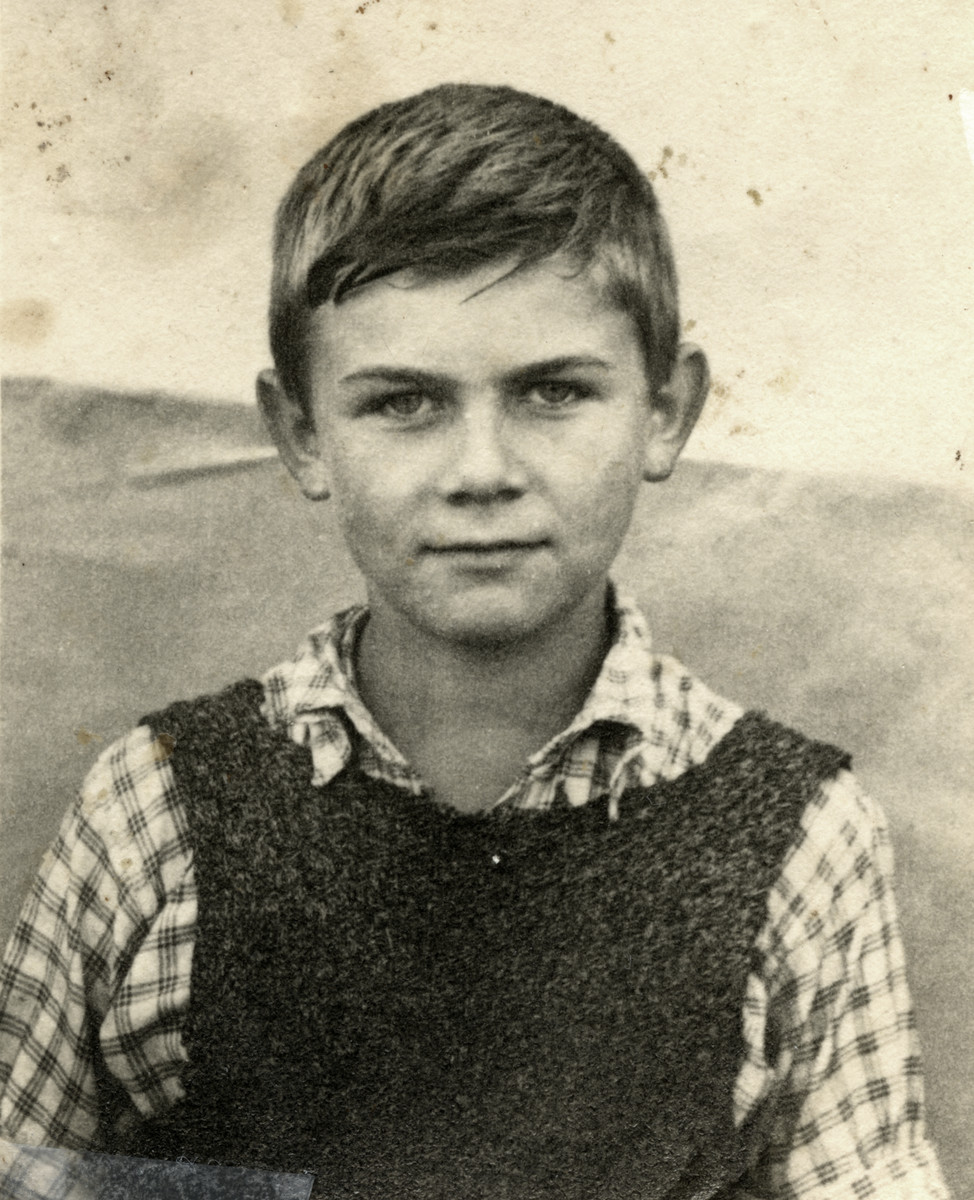 Portrait of child survivor Ziomek Hammer.  He is wearing a vest that his mother knitted for him; it was the only warm piece of clothing that he owned and which he wore throughout the ghetto and while in hiding.