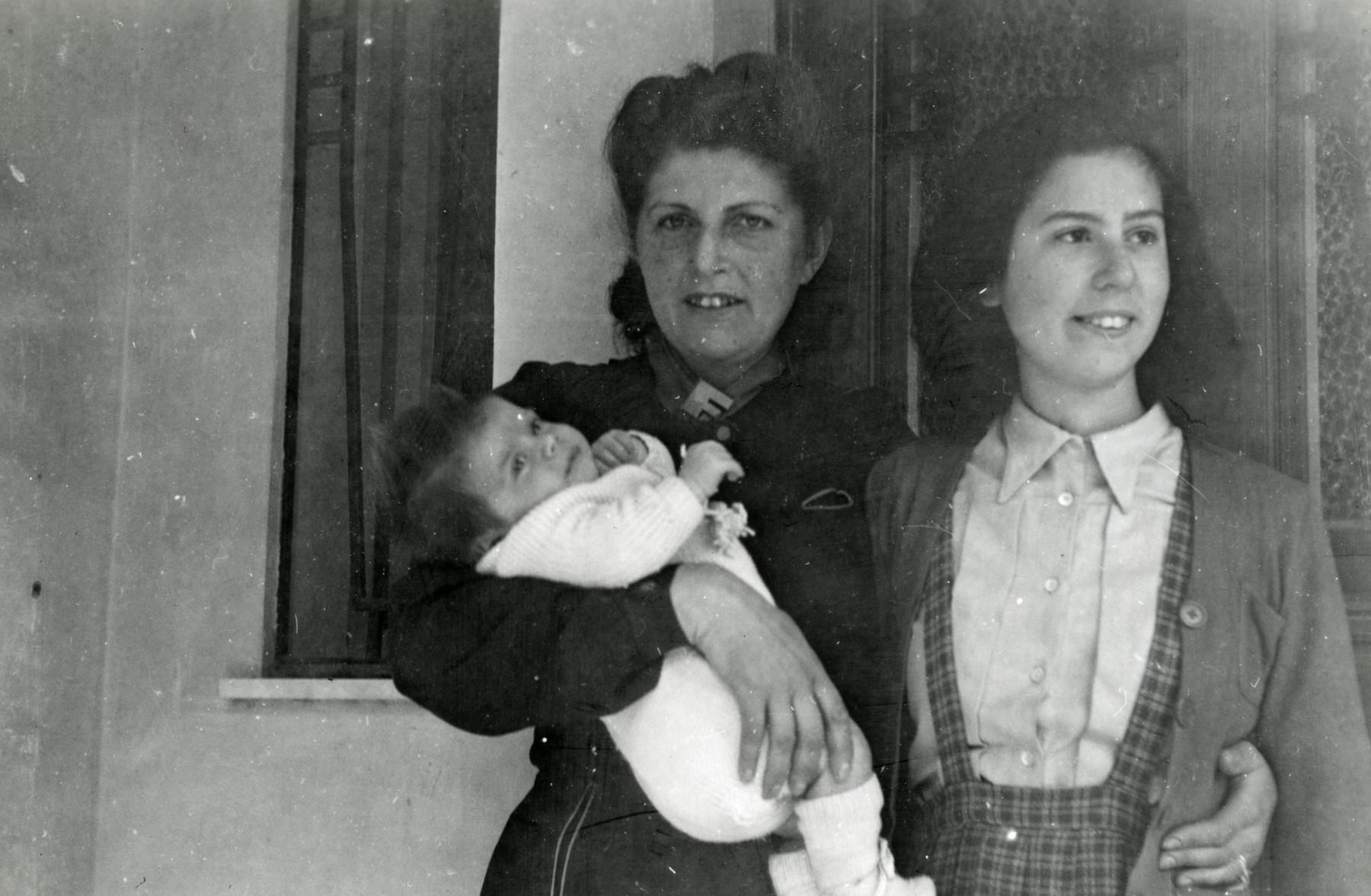 Luba Spiegelglass Fainas holds her newborn son Georges while standing next to her older daughter Renee.