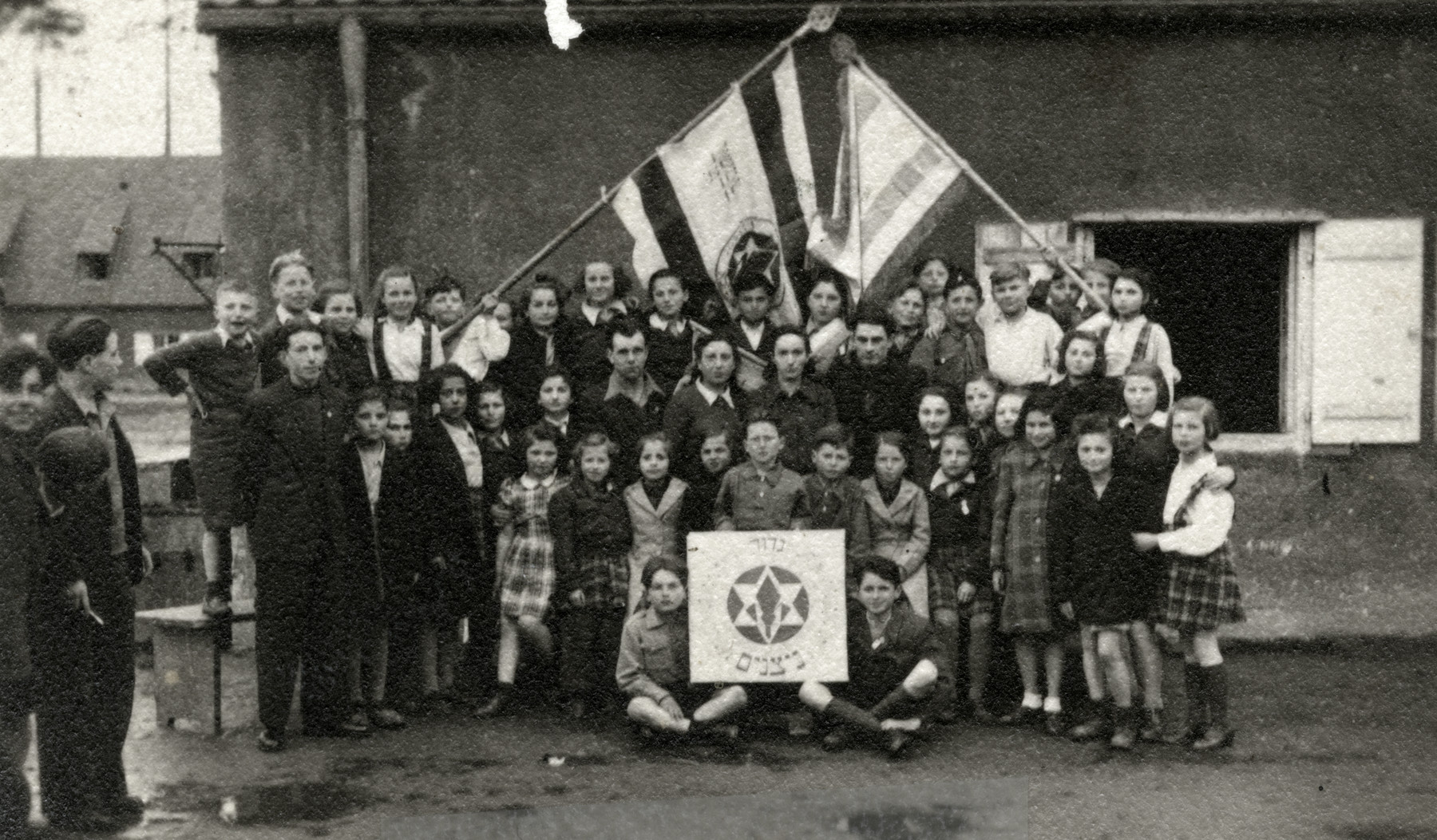 Zionist youth belonging to the Nitzanim group of Hashomer Hatzioni pose underneath two flags.  Ziomek Hammer is pictured in the top row, fourth from right.