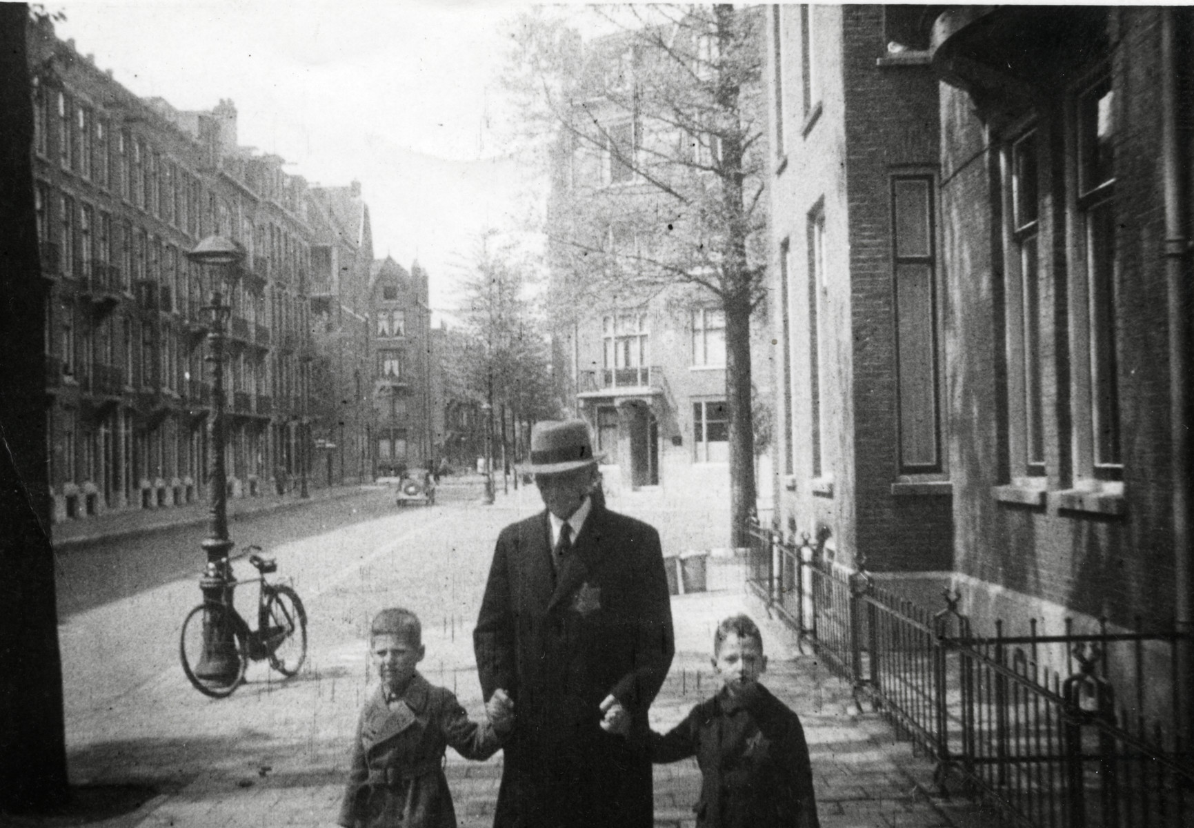 Hartog Kisch walks down the street with his two grandsons Eldad and Hanan .  The grandfather and Eldad are both wearing Jewish stars.  Eldad was not required to wear a Jewish star but wanted to anyhow.