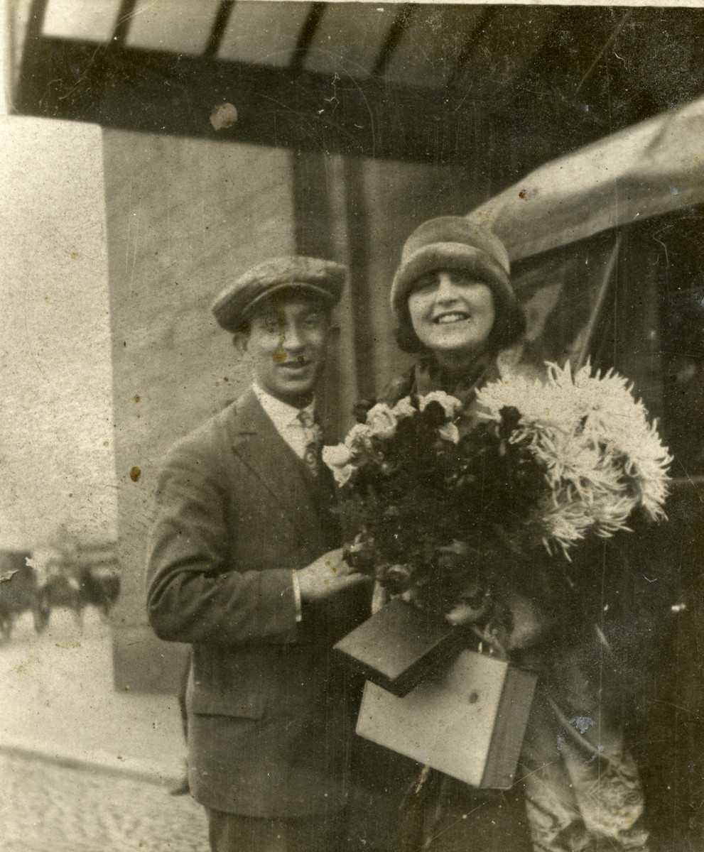 Close-up portrait of Luba and Alexander Fainas; she is carrying large bouquets of flowers.