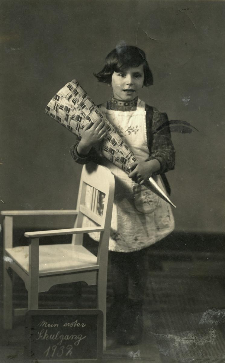 Studio portrait of Regina Birnbaum holding a cone of goodies on her first day of school in Berlin.