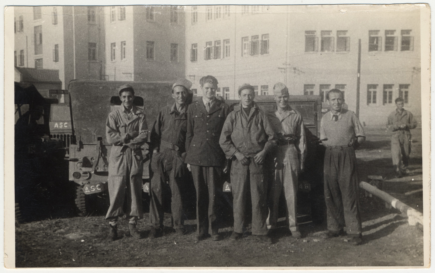 Group portrait of American soldiers and Jewish refugees standing outside next to parked military vehicles in Shanghai.