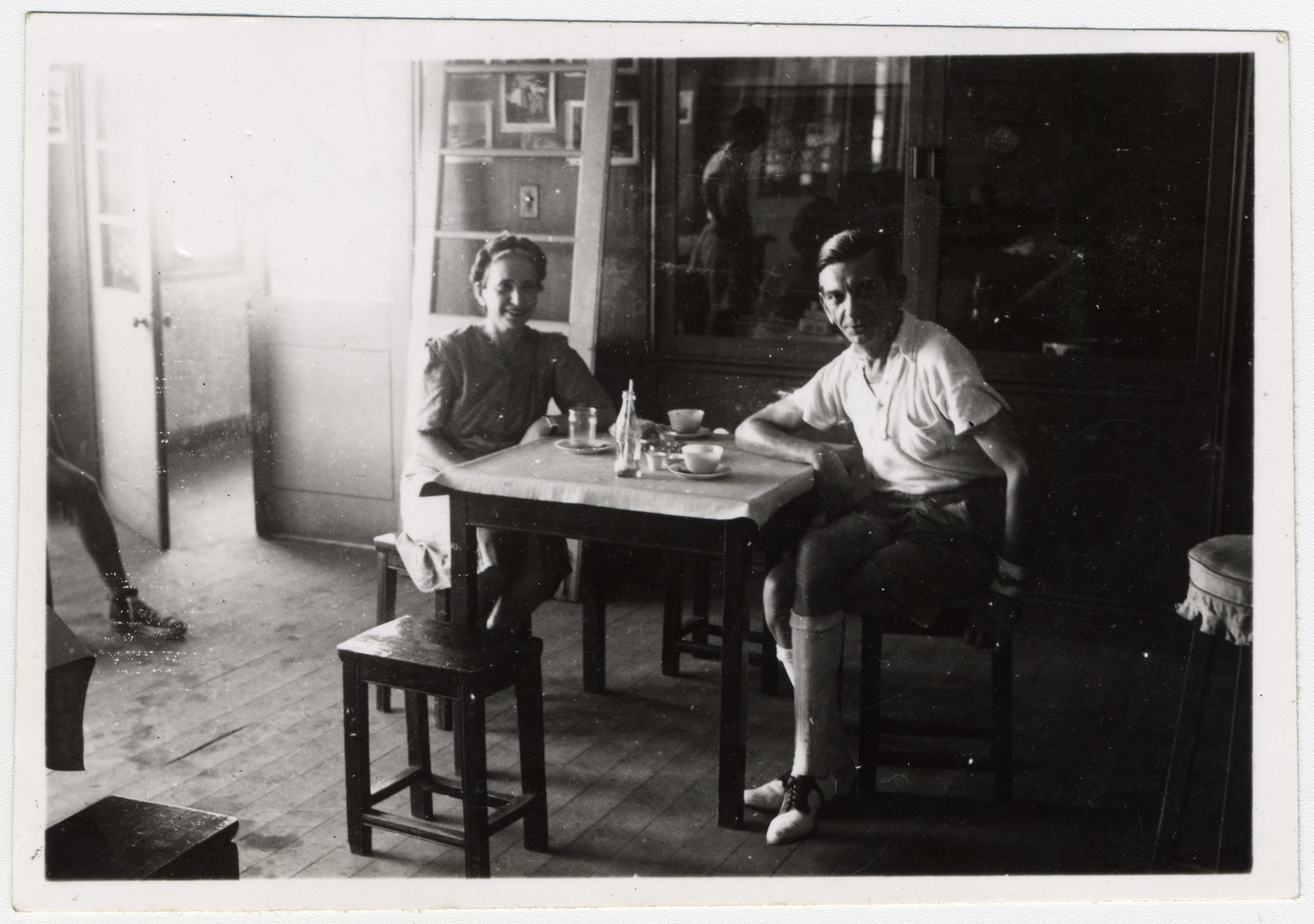 Gertrud and Alfred Heller sit at a table inside the Shanghai Jewish Community Center.