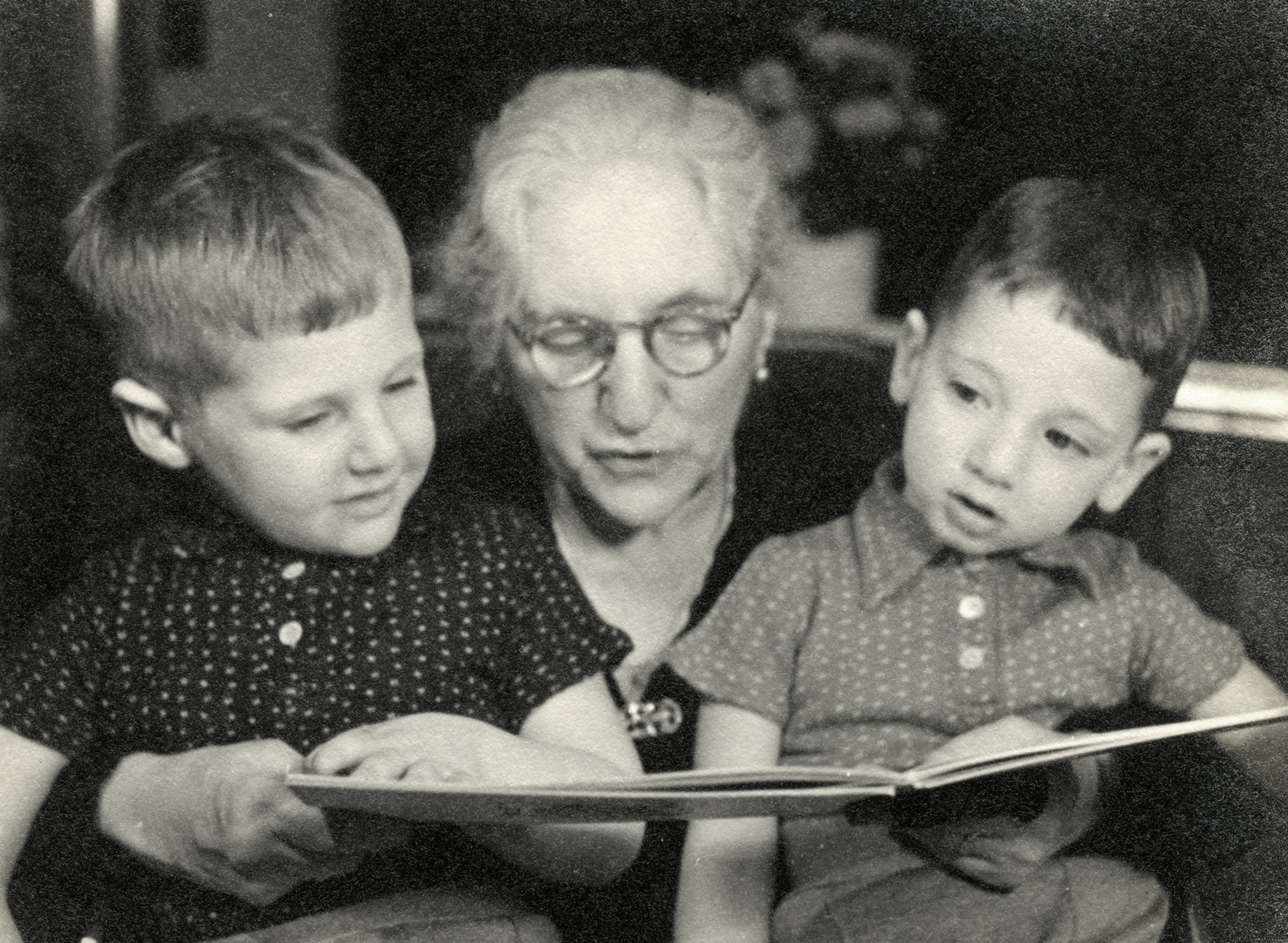 Hanan and Eldad Kisch sit on their grandmother's lap and listen to her read a book.