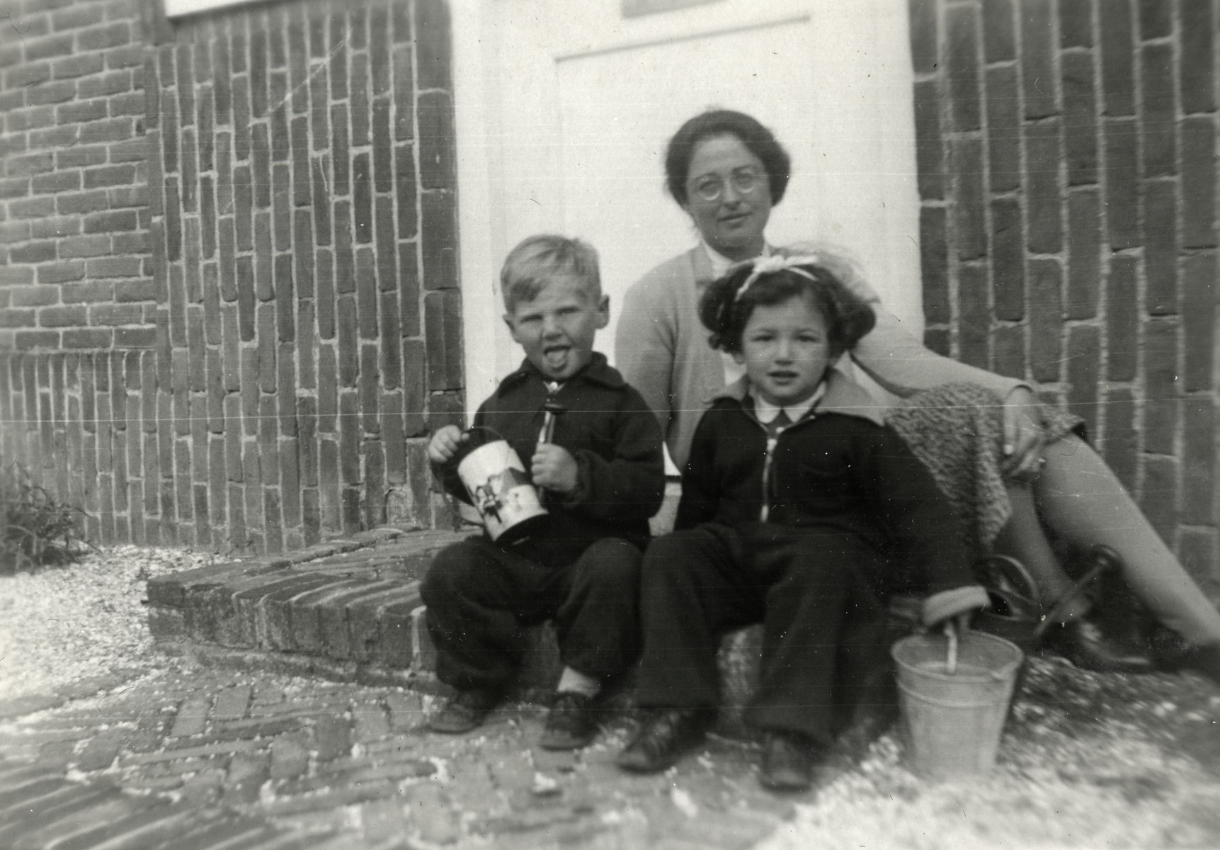 Hanan Kisch sits on the stoop of a building with his cousin Lin de Bruin and her daughter.  Lin de Bruin came to Palestine as part of a prisoner exchange for Templars with her daughter. (Her husband committed suicide in 1940).