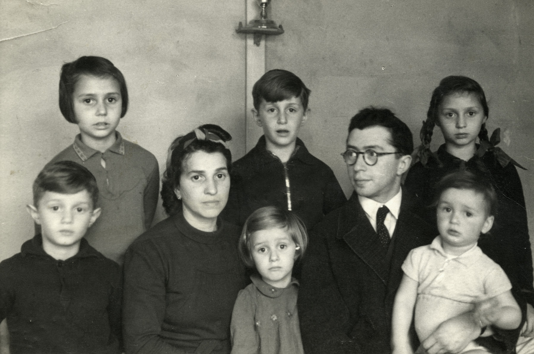 Portrait of the entire Birnbaum family in Westerbork.   Pictured from left to right are Zvi, Sonni, Hennie, Yaakov, Susy, Yehoshua, Regina and Shmuel.