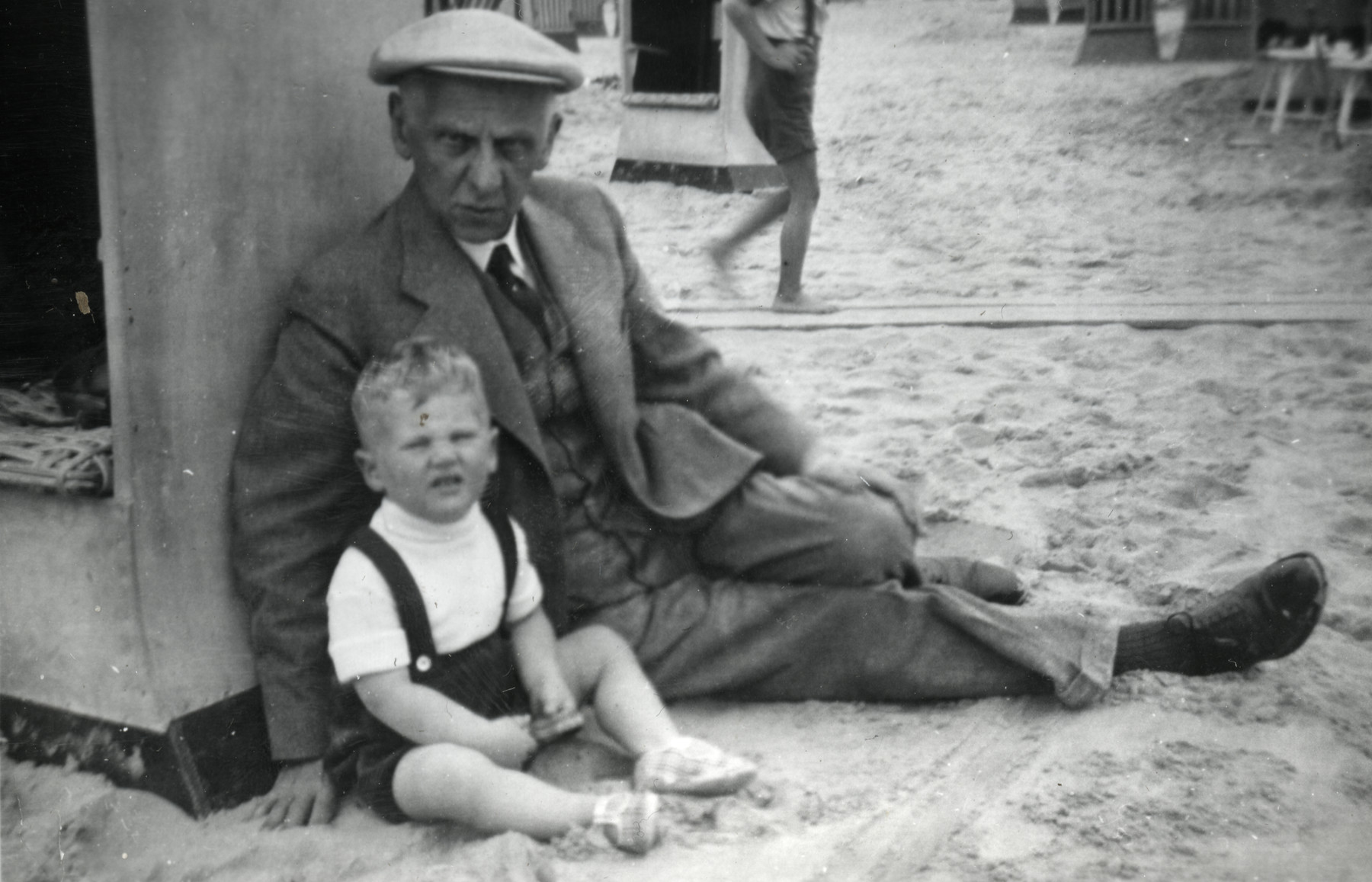 Hanan Kisch sits next to a beach cabana with his grandfather, Hartog Kisch.