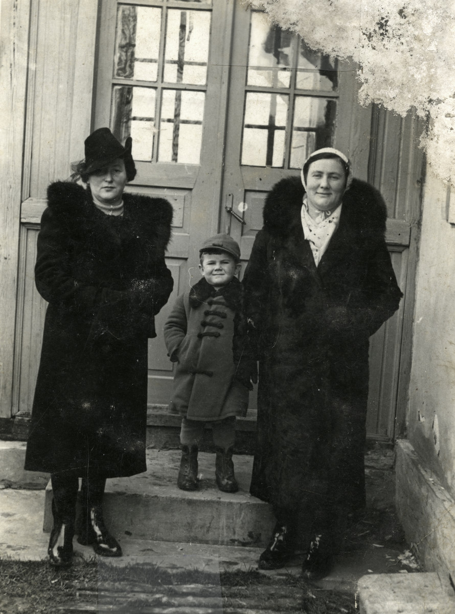 Prewar portrait of Ziomek Hammer stands outside the entrance to a building with his aunt and mother.  From left to right are Rivke Tempel, Ziomek Hammer and Lola Hammer.