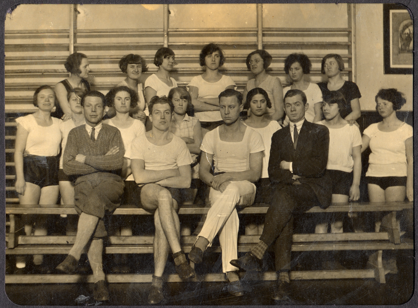 Members of a Deaf gymnastics club pose for a group portrait on the bleachers.  Among those pictured are Hilda Wiener (back row, far left) and Isadore Rattner (front row, second from left).