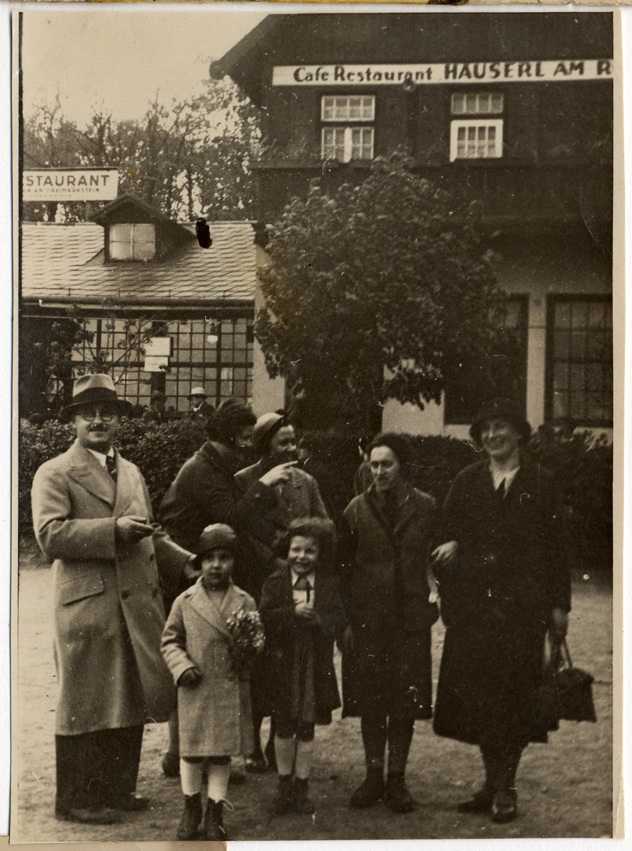 Austrian Jewish friends and family pose for a photograph in front of a restaurant in Vienna.  Among those pictured are Mr. and Mrs. Antler (first and second from the left), their daughter Heidi (front, holding flowers), Hilda Wiener Rattner (far right), and her daughter Nelly (front center).