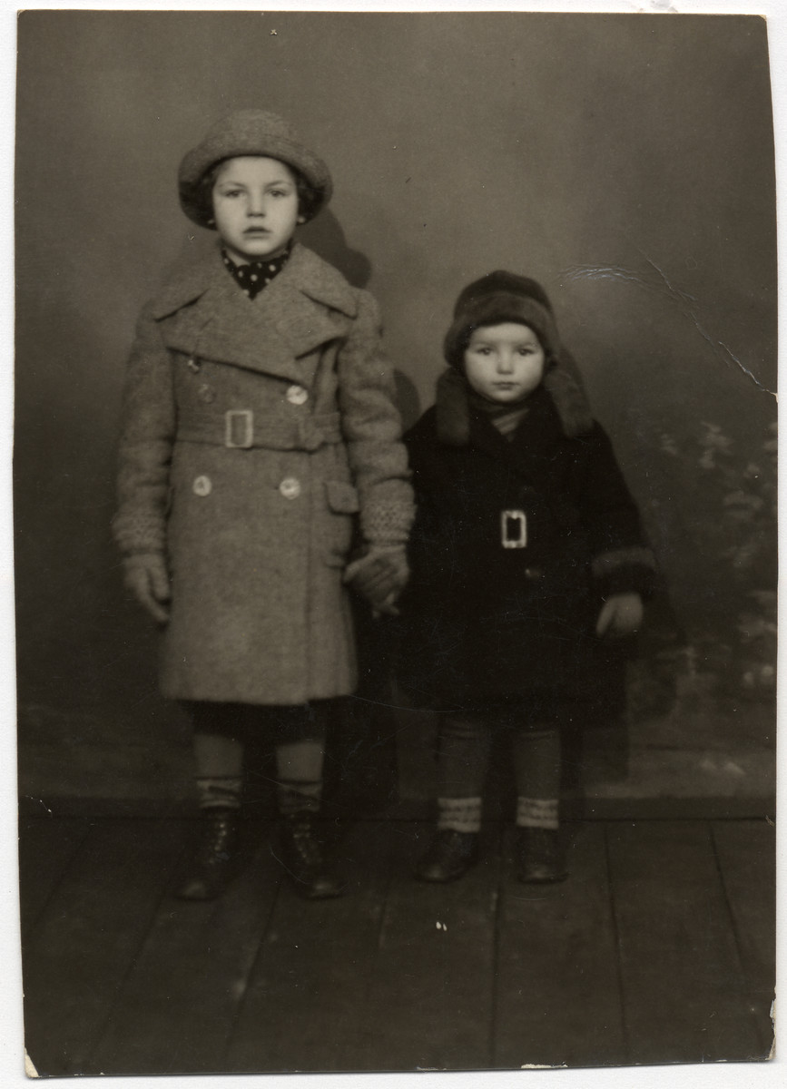 Portrait of sisters Nelly and Lilly Rattner, wearing coats made for them by their uncle Richard, a tailor.