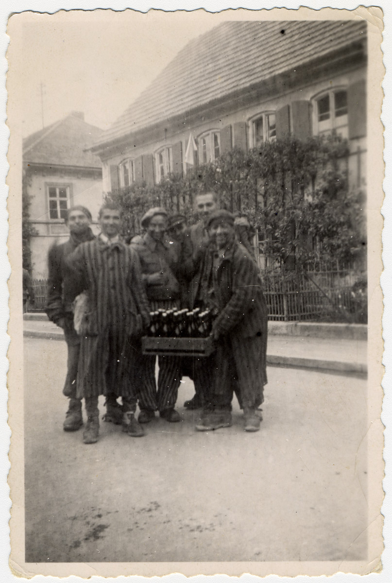 Jewish survivors from Kaufering I carry a crate of bottles right after their liberation by the American army.  According to the donor, they had broke into surrounding houses and found either beer or wine which they gave to the American soldiers to thank them.