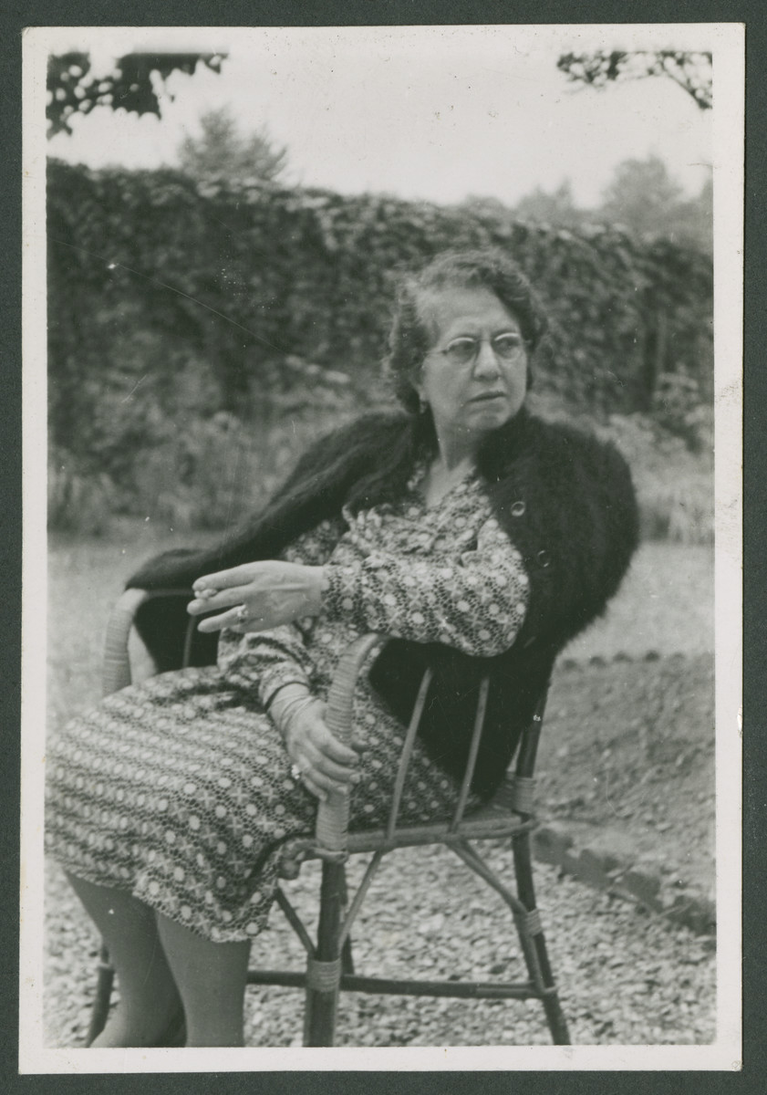 The mother of Jacque Arditti sits outside on a wooden chair.  [The photo was probably taken in Nice but the date and locale are uncertain.]