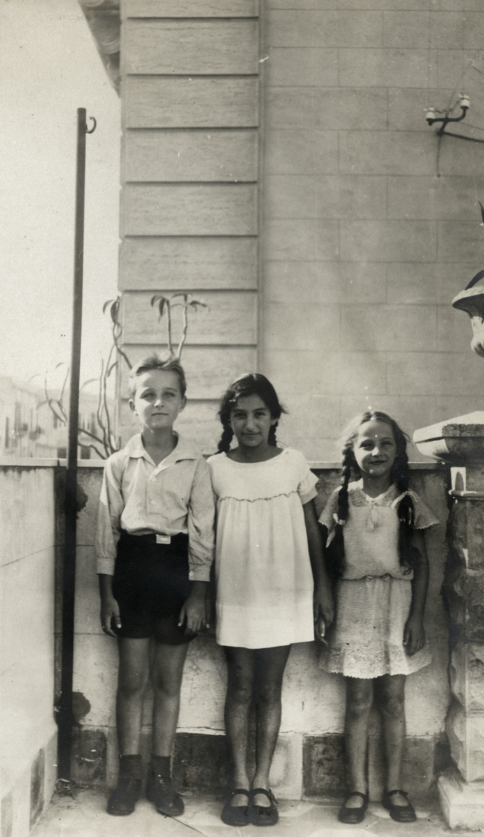 Portrait of three children standing on a porch in Palermo.  Pictured are Luigi and Anni Beretras with an unidentified friend (middle).