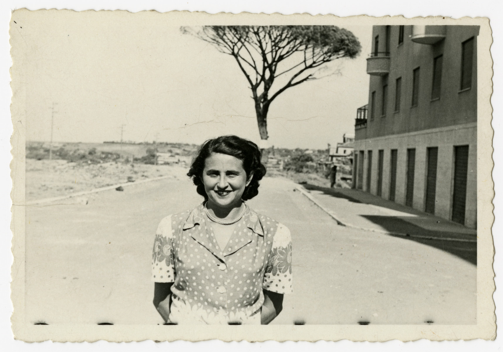 Elsa Herlinger stands outside their first apartment following liberation.