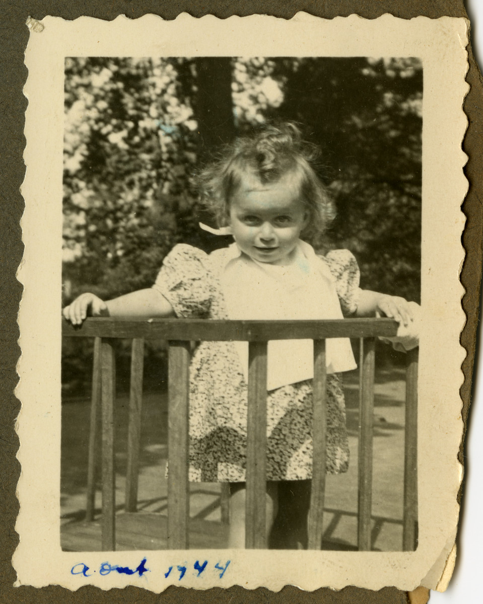 Close-up of Marguerite-Rose Birnbaum standing next to a small fence while in hiding with the Dinq family.