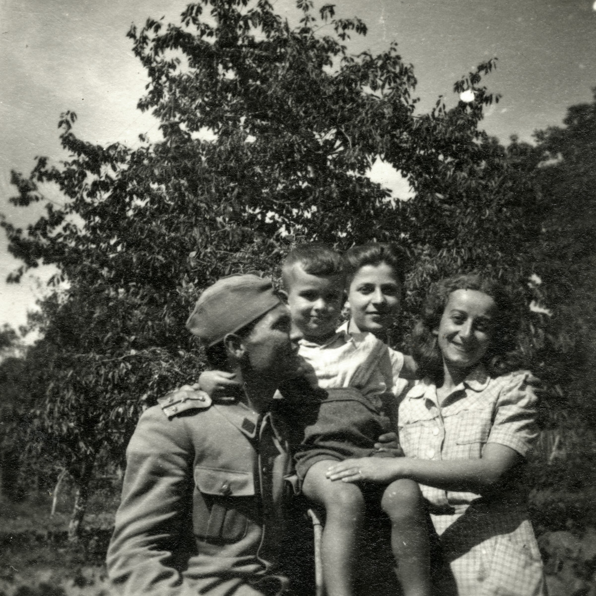 A group of friends, one in military uniform pose outside after the war.  Donna Papo is pictured on the right.