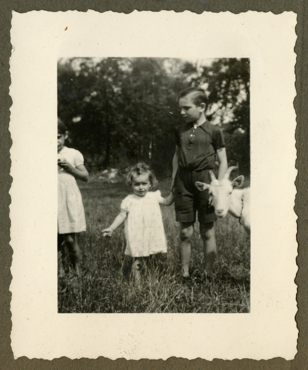 Marguerite-Rose Birnbaum holds hands with Marcq Dincq, the son of her rescuers, Pierre and Marie-Josephe Dincq while a goat stands to the side.