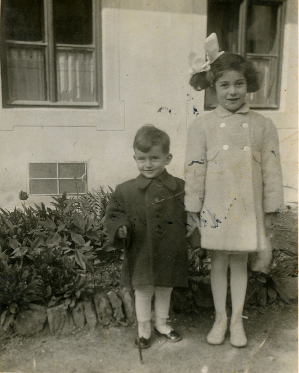Siblings Villiam and Helene Doris Krausz stand outside their family's home in Nitra.