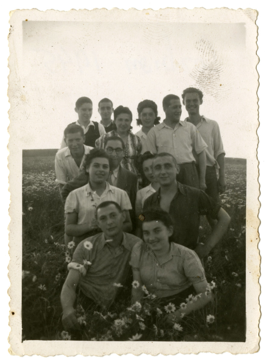 Group portrait of Jewish displaced persons in Corbion, Belgium.  Hanka Wajcblum is kneeling in the second row on the left.  Alex Cige is kneeling in the second row on the right.  Marta Bindiger Cige is sitting in the first row on the right.