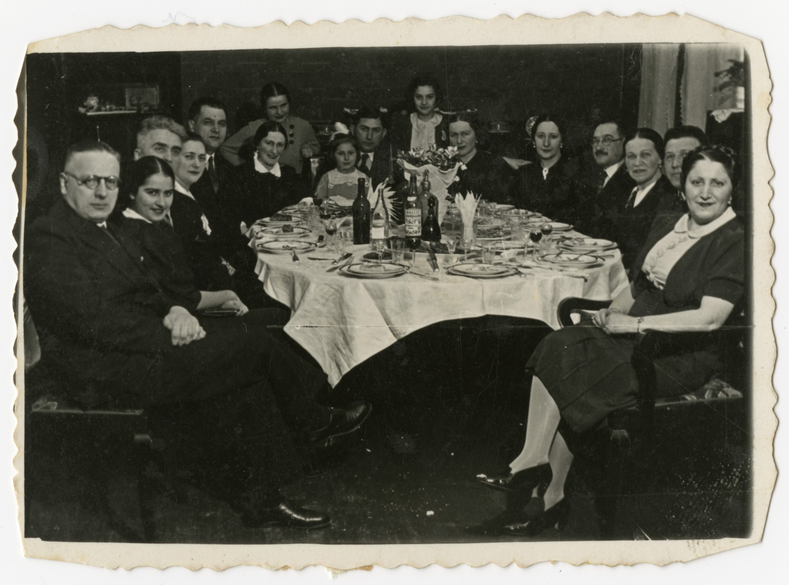 The Wajcblum and Jaglom families gather for a Passover seder in Brest.  Estusia Wajcblum is standing in the center, rear.  Seated at the head of the table is Moise Jaglom is holding his daughter Jeannette.  His wife Klara  is on the right with the pearl earrings.