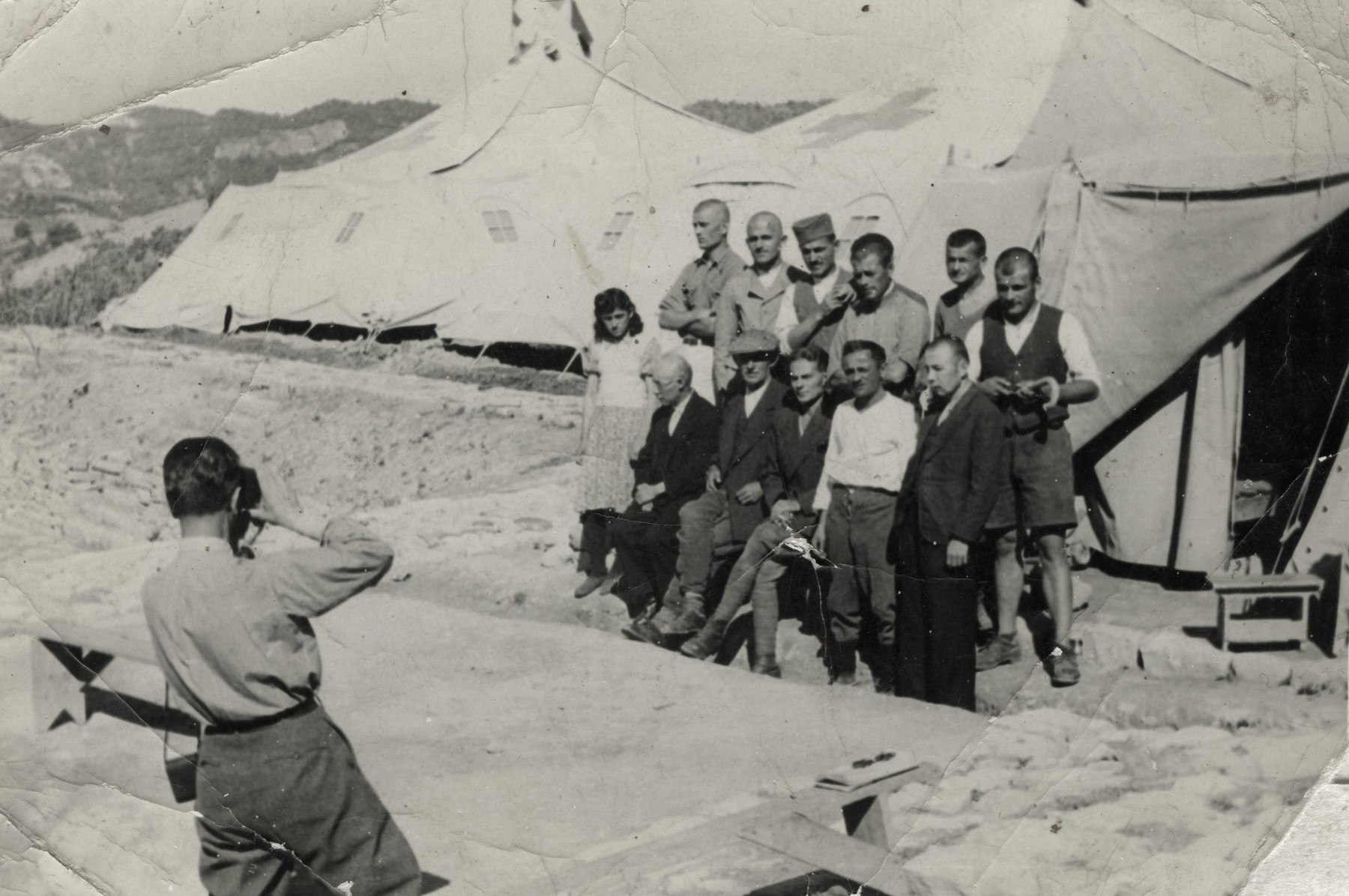 An Italian soldier takes a photo of a group of prisoners outside a tent in the Preza labor camp.  Dr. Joseph Teitelbaum is setting in the front row, left.