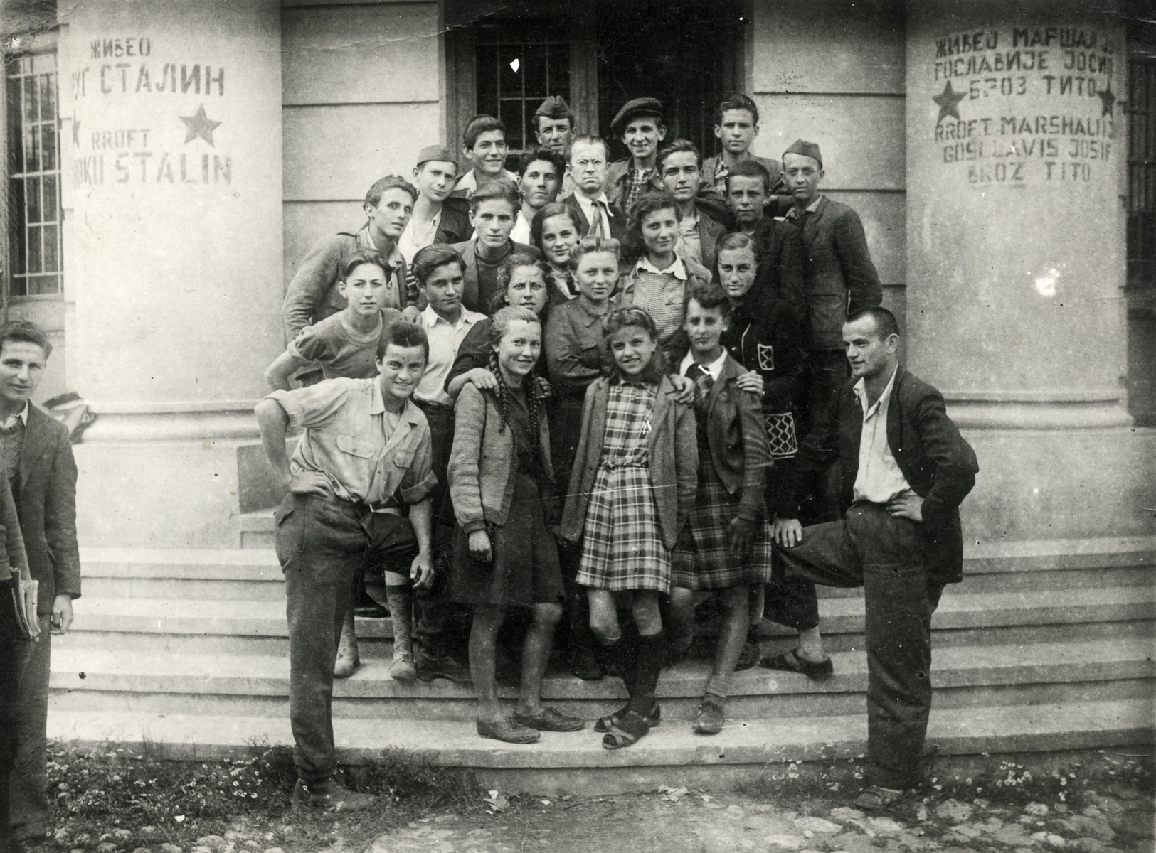 "Group portrait of high school students in Prizren, Albania.  Raul Teitelbaum is standing in the second row on the far left.  The graffiti on the walls reads ""Long live Stalin,""  ""Long Live Tito."""