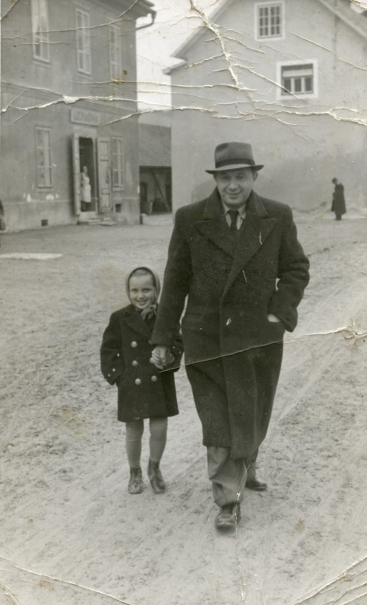 Miriam Steiner and her father walk down the street in front of the pharmacy where he works.