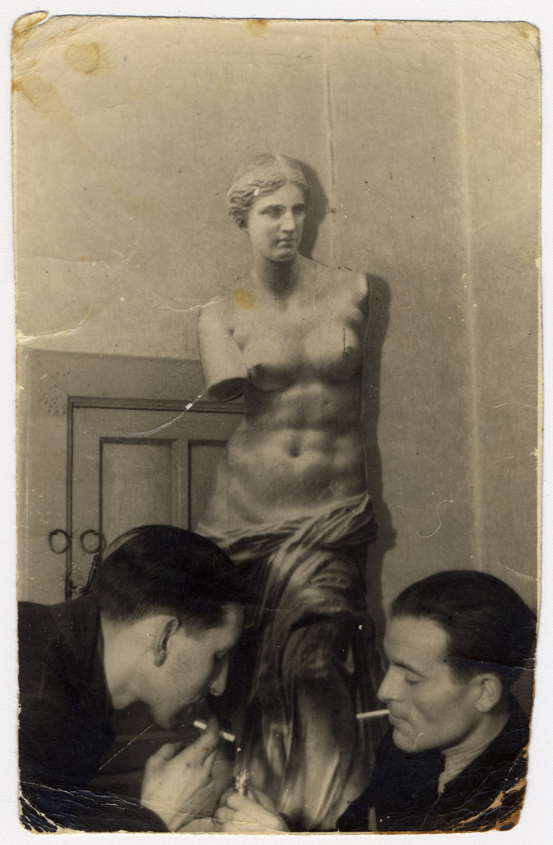 Two Jewish men light cigarettes in front of a carboard replica of the Venus de Milo which is part of an art exhibition in the Lodz ghetto.   Pictured are Josef Szwarc (later Schwartz) and his brother Pinchas Szwarc (later Shaar).