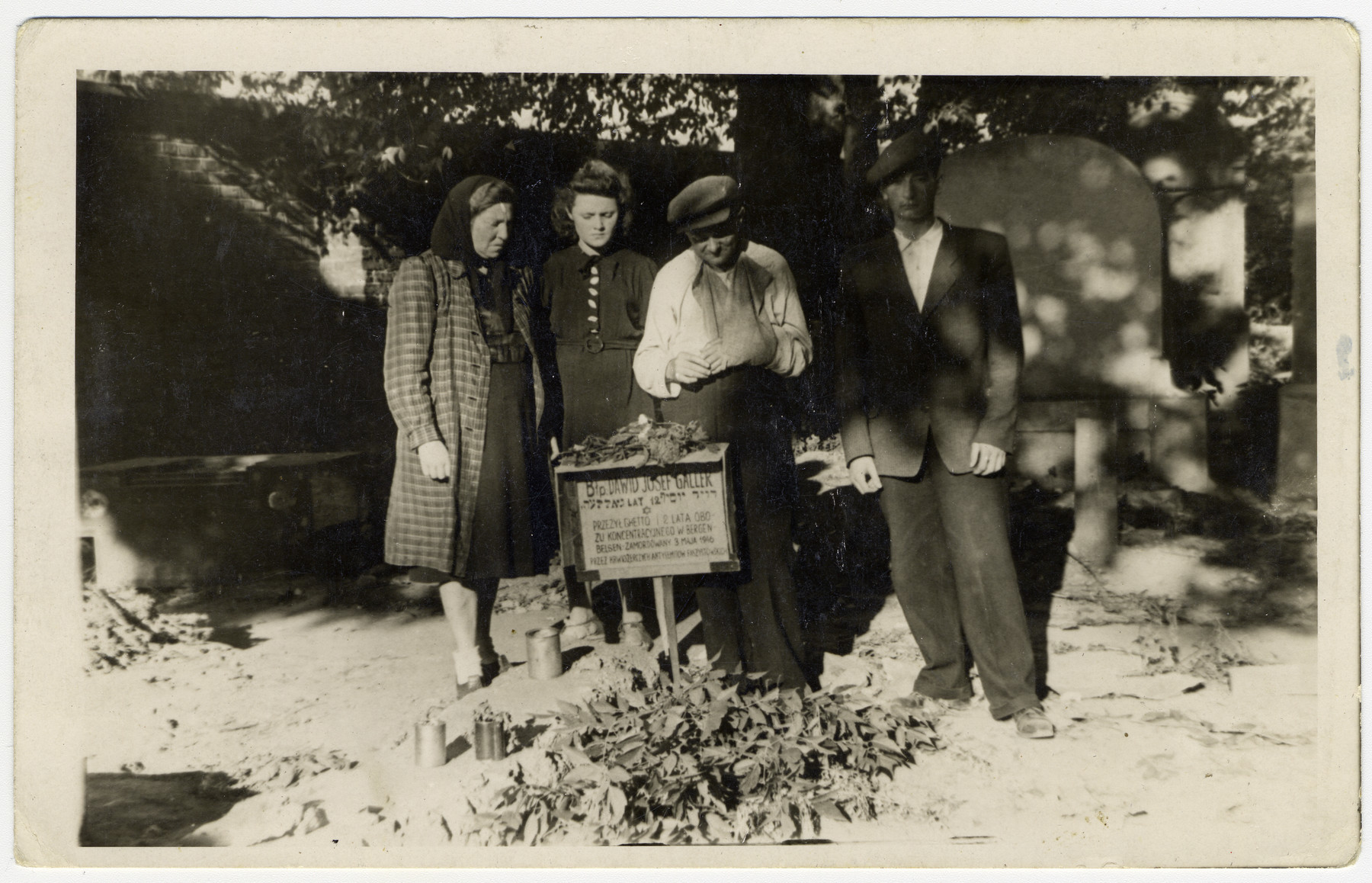 The Galler family stands by the grave of Jews killed in a postwar attack on members of the Zionist group Gordonia outside of Krakow.  Among those killed was Yosef Galler.  Pictured are Maria Galler (his mother), Renna Galler (his sister) and Izrael Galler (his father).  The man on the far right is unidentified.  The family survived Bergen-Belsen on Argentinian papers and were liberated on the train in Fallersleben.