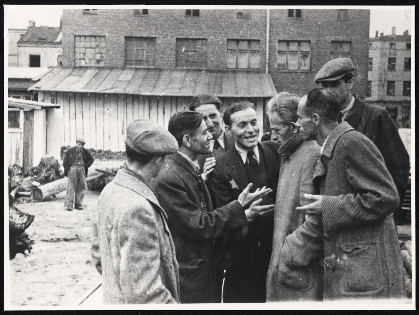 A group of Jewish men have a conversation in front of one of the ghetto factories.   Among those pictured, in the middle, is donor's husband, Pinchas Szwarc and behind him may be his brother Josef.