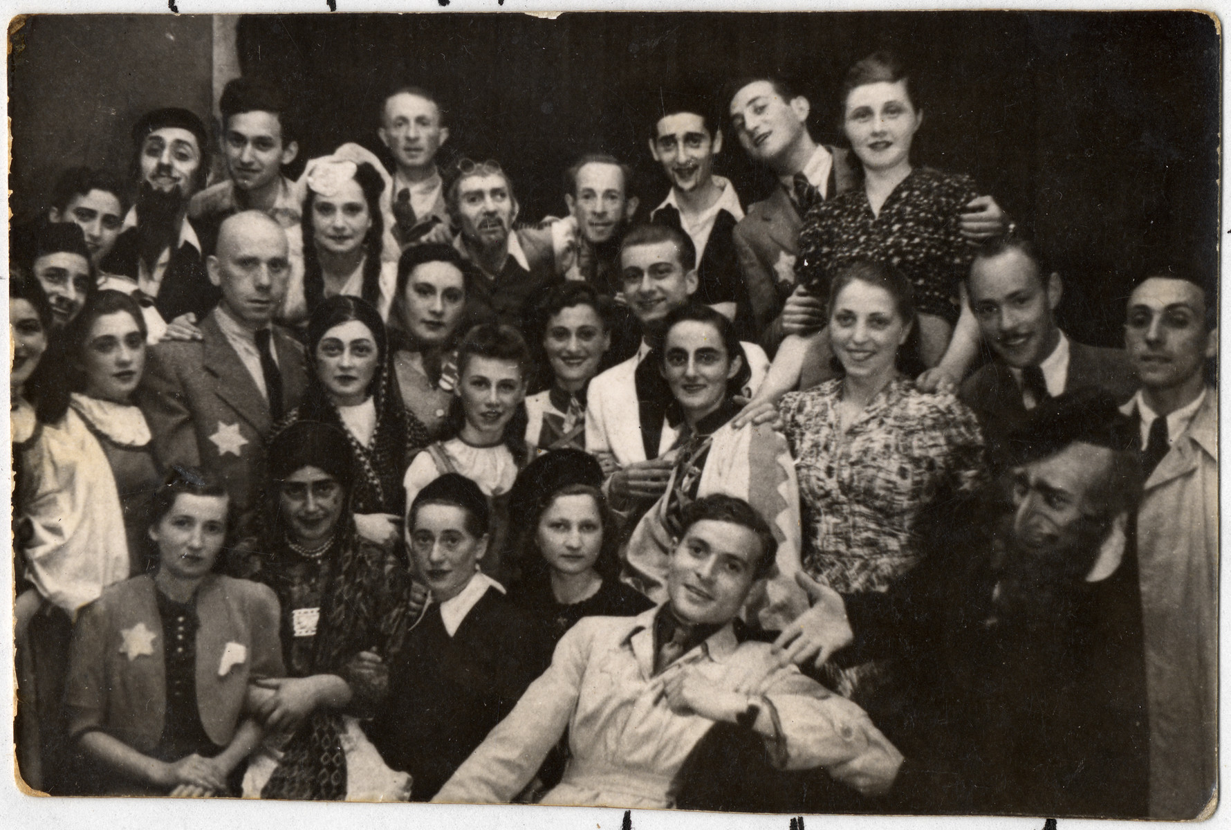 Group portrait of members of a theater group, some in costume, in the Lodz ghetto.   Fifth from the left in the first row may be donor's late husband, Pinchas Szwarc (later Shaar), who designed the stage decorations.