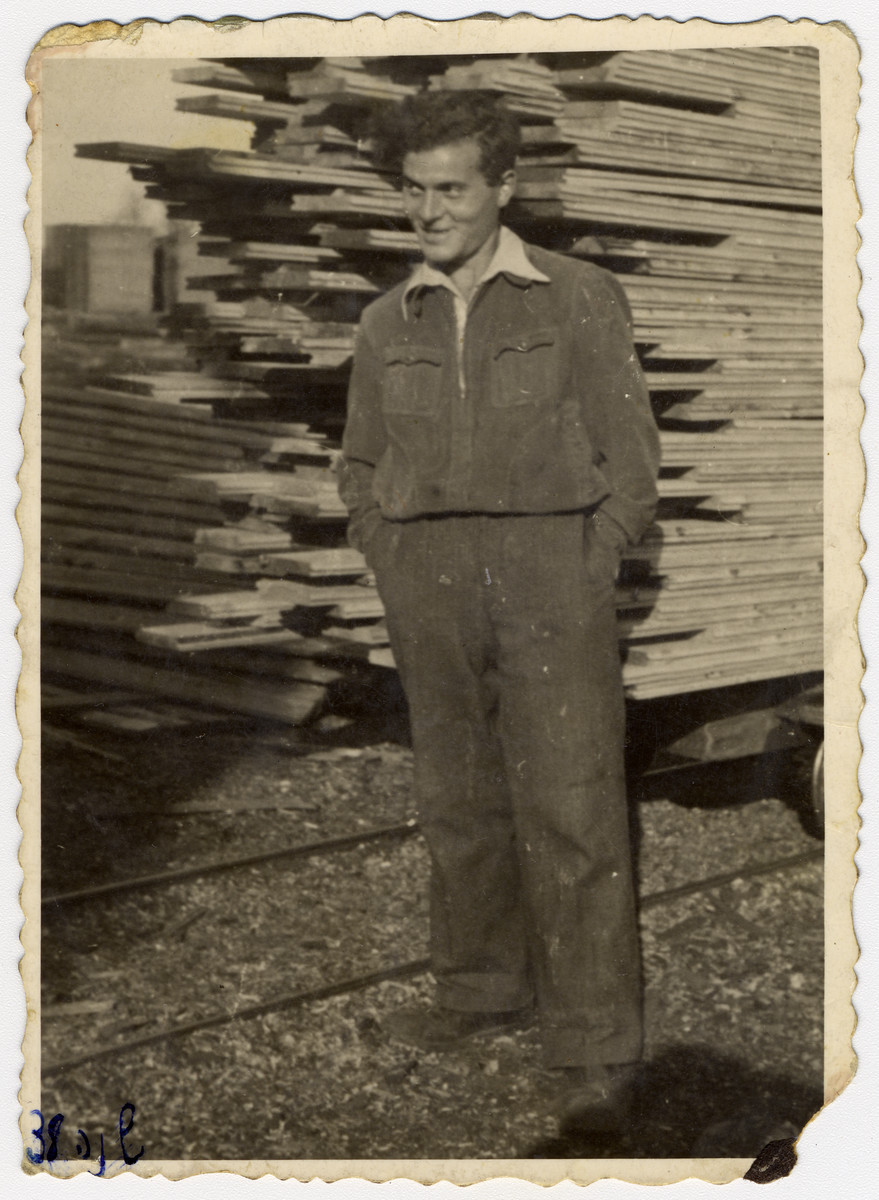 Close-up portrait of a young man standing in front of a stack of wooden boards.   Pictured is Pinchas Szwarc (later Shaar) possibly in his father's lumberyard.