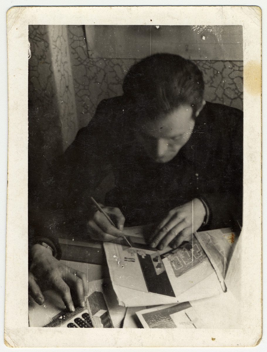 Pinchas Szwarc (later Shaar) works at his desk in the statistical department of the Lodz ghetto.