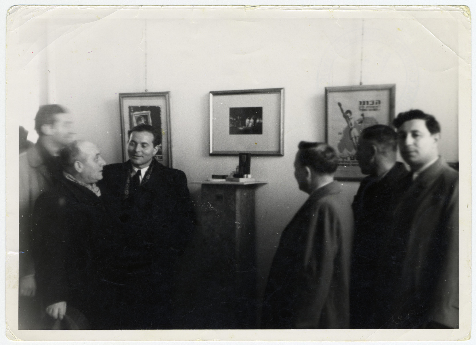 A group of men views an exhibition of paintings by artist Pinchas Szwarc (later Shaar).   Among those pictured, second and third from the left, are Jakub Szwarc and his son Pinchas Szwarc.