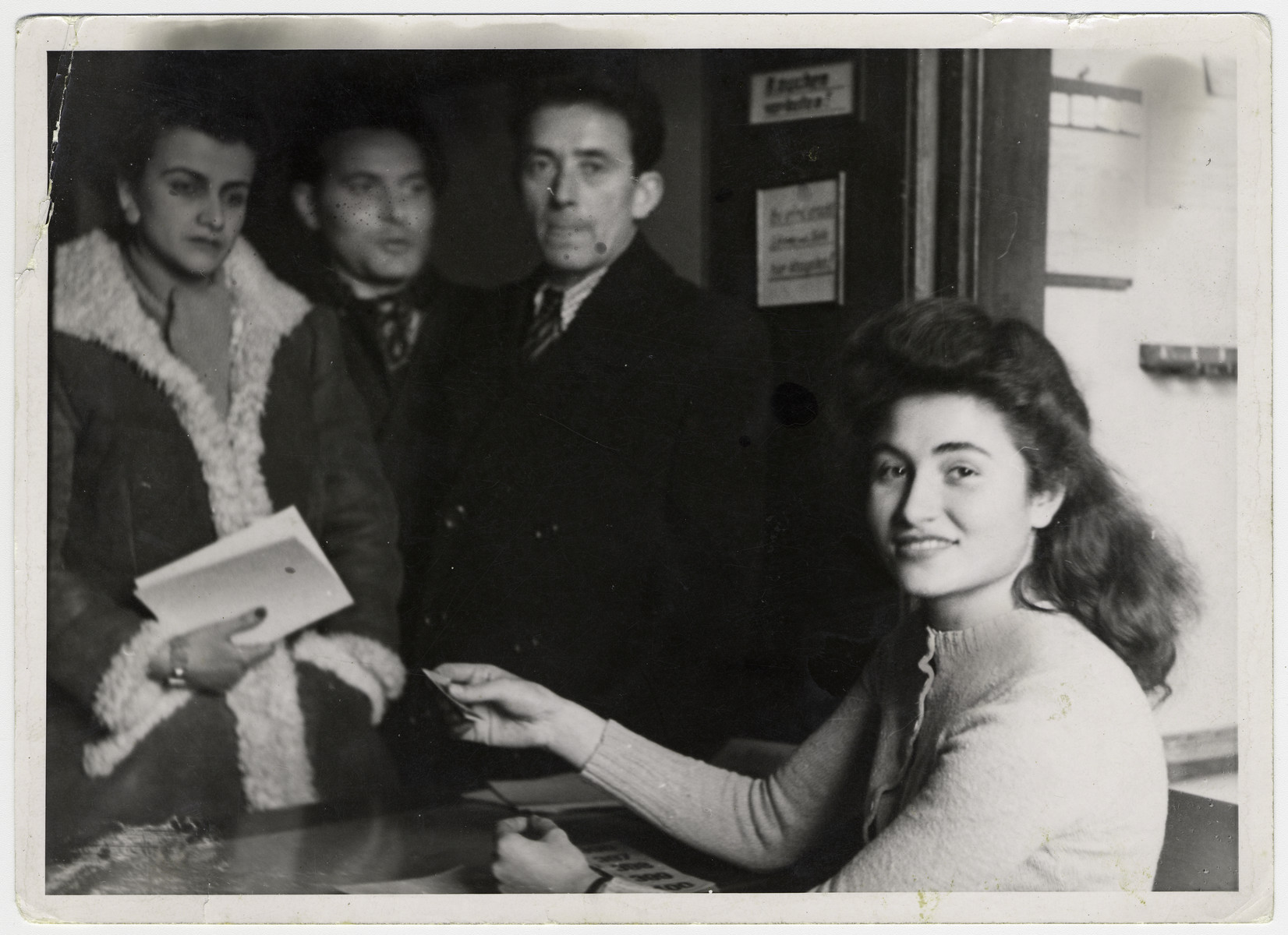 A woman sells tickets at the entrance to Pinchas Shaar's paintings exhibition in Munich.  Pictured, from the left, are donor's husband, Pinchas Szwarc (later Shaar), Hirsch Szylis and Ruth Kardoso-Vaelkel (on the right).