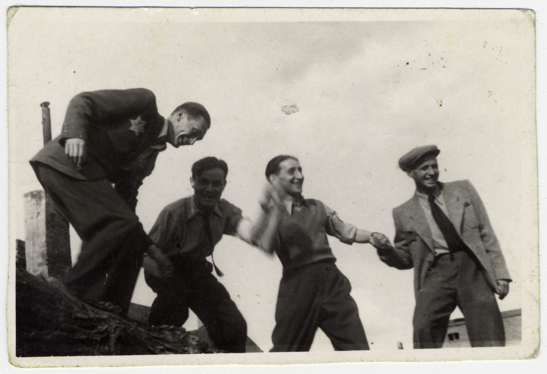 Four Jewish young men hold hands in the Lodz ghetto.   Second and third from the left are Pinchas Szwarc (later Shaar) and his brother Josef Szwarc (later Schwartz).