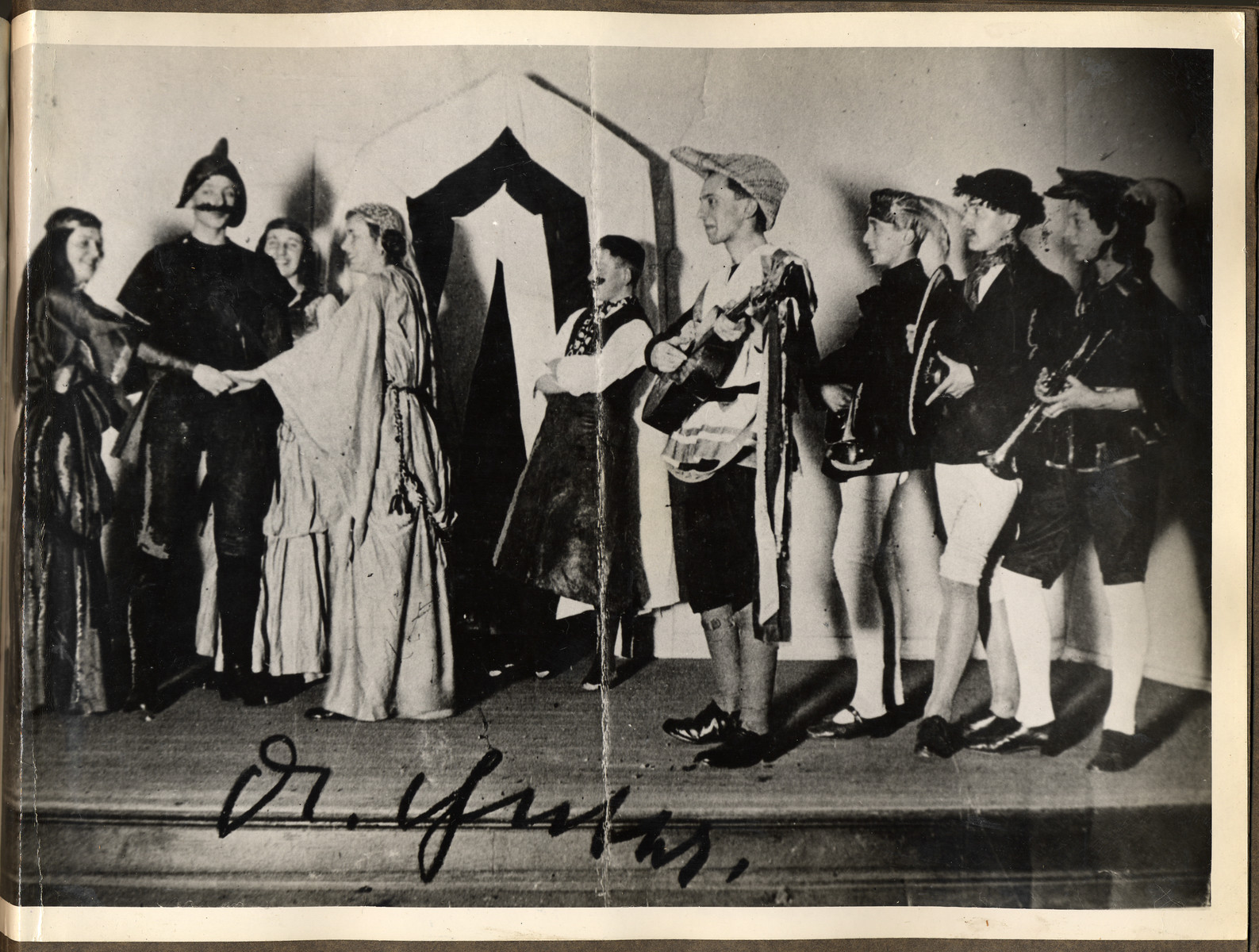 "Joseph Goebbels performs in a school theatrical.  The orginial American caption reads: ""Do you know him - the actor in the center playing a guitar? He is Joe Gobbels, acting in a school play in his native town of Rheydt, Germany. The picture was taken of a schoolmate of Dr.Gobbels, who had it autographed when the latter visited his hometown of Rheydt shortly before the American troops captured the city. He started early as an actor, Joe Gobbels but he will soon lose his job."""