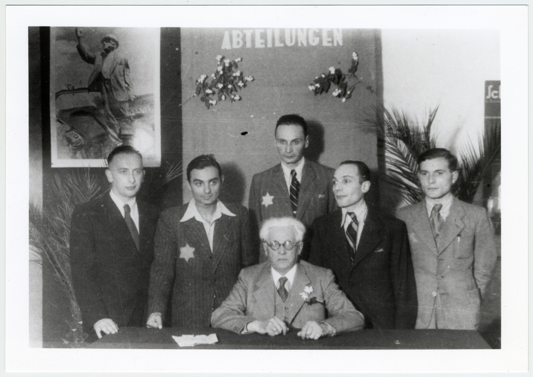 Mordechai Chaim Rumkowski and other officials pose for a group portrait by a desk underneath a banner and a large portrait of Rumkowski.  Among those pictured, on the far right, is donor's husband, Pinchas Szwarc (later Shaar), and second from the left is Henryk Neftalin who was responsible for many of the ghetto's administrative branches including the registration bureau, the department  of statistics, the Rabinical bureau, and the photography studio as well.