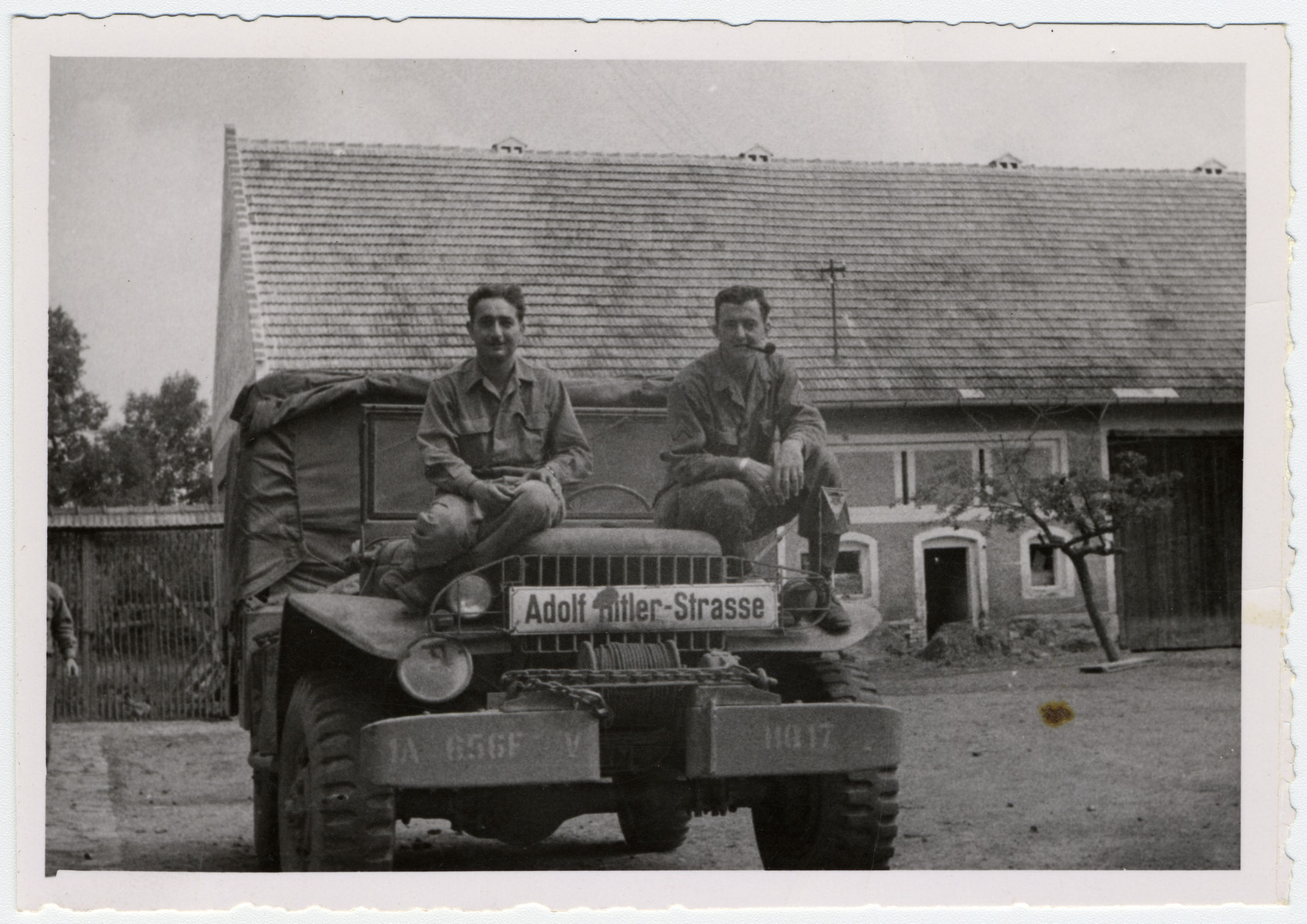 Two American soldiers ride on a military car decorated with a confiscated Adolf Hitler Strasse street sign.