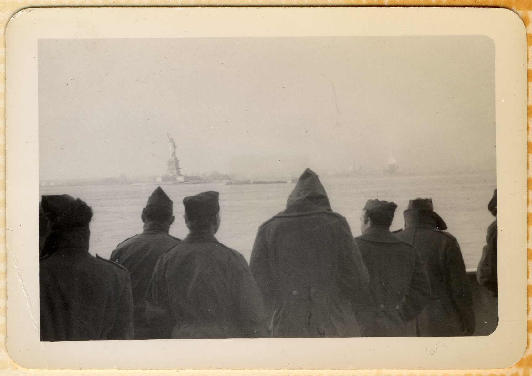 American GIs stand on the deck of their troop ship and look at the Statue of Liberty as they pull into NY harbor on their return home from World War II.