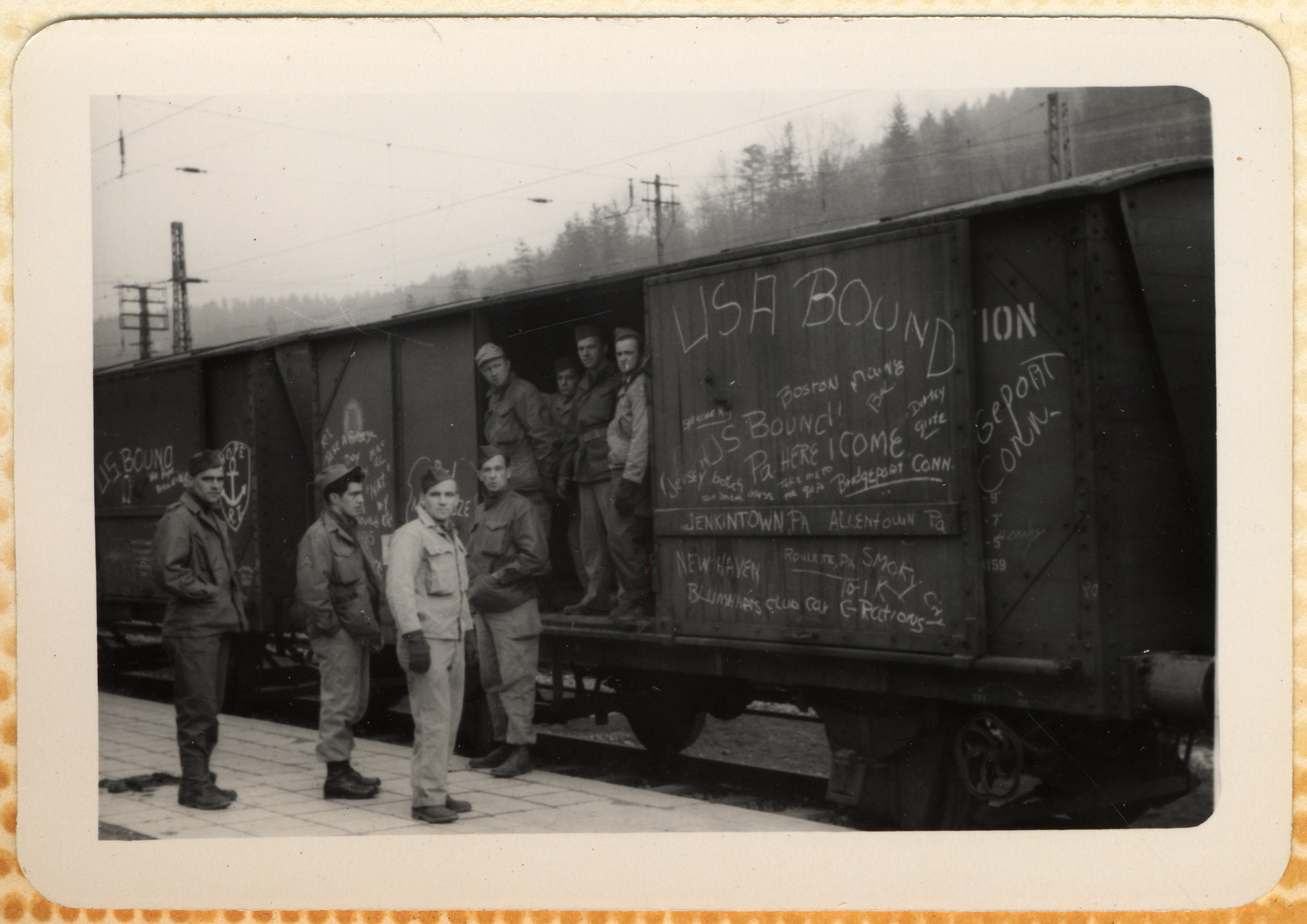 """American GIs prepare to return home.  They are standing by a train with the words """"USA Bound"""" written on its side."""