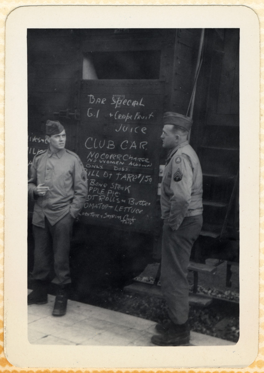 "Two US servicemen stand next to a sign on a train labeled ""Bar Special; GI Club Car."""