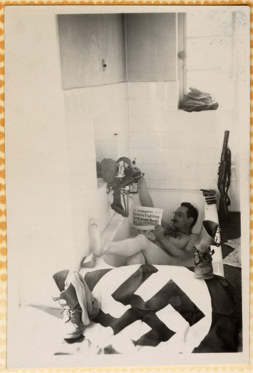An American soldier reads a newspaper about the Soviet occupation of Berlin while relaxing in a bathtub decorated with a former Nazi flag.  The father of the donor bought this photo from another soldier.