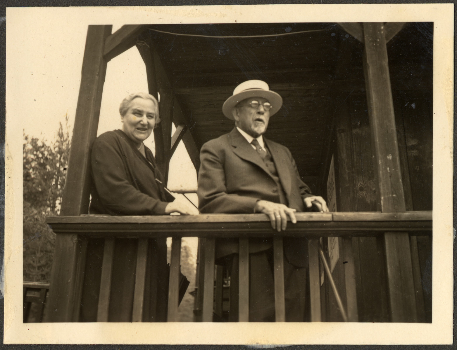 Bela and Leo Stern (the great-grandparents of the donor) pose on the balcony of a wooden building.