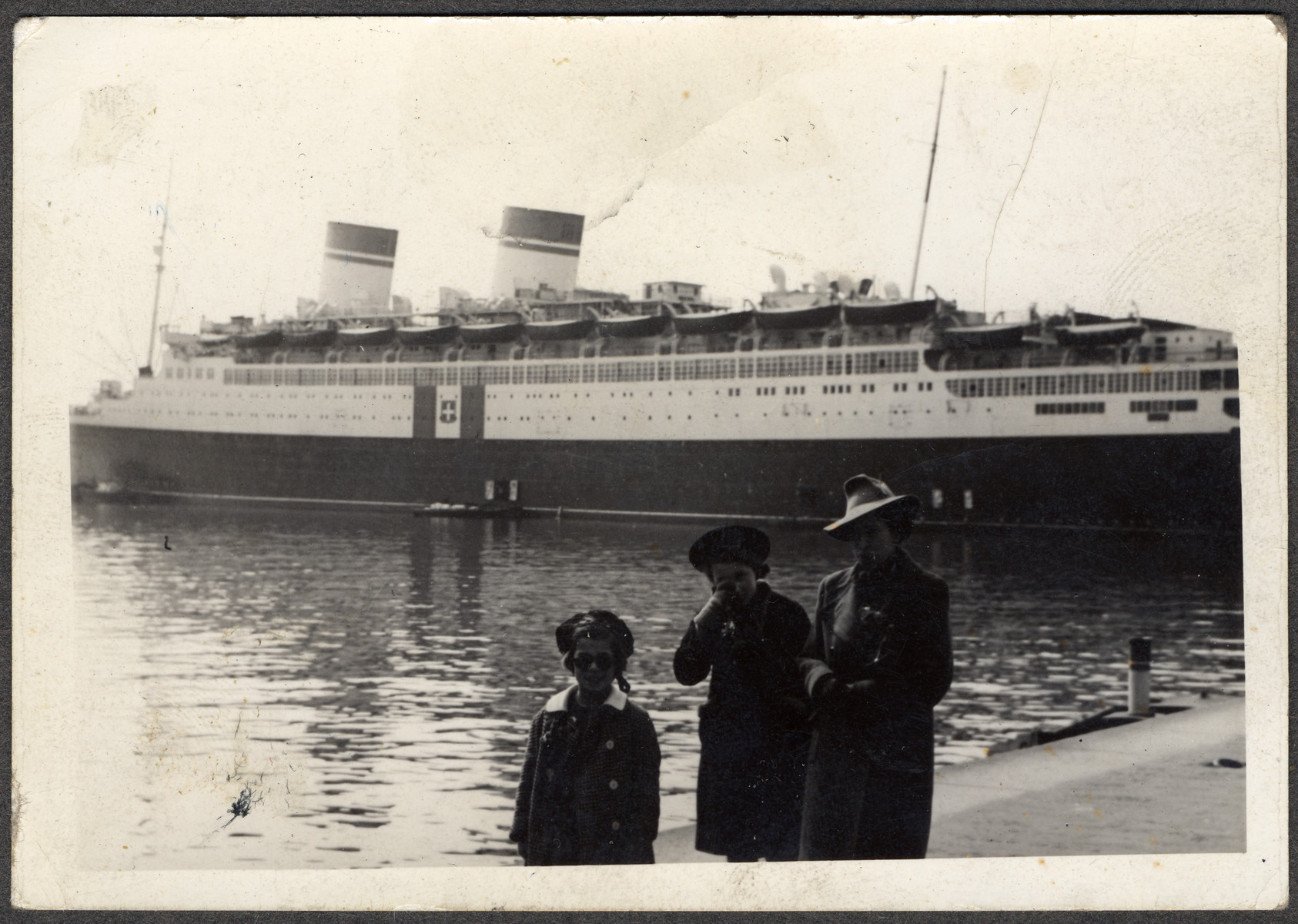 The Seligman family  pose in front of the ship that  would take them to the United States.   Pictured (left to right) are Margit, Ellen, and Rose Seligman.